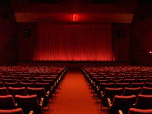 Photographie d'un théâtre avec un rideau et des sièges rouges