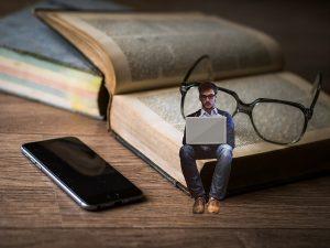 Image d'un livre, de lunettes et teléphone et un petit homme asis sur le livre un ordinateur sur les genoux