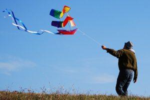 photographie d'un homme tenant un cerf-volant