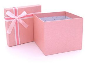 une boite cadeau rose avec ruban