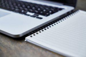 Photographie d'un ordinateur portable à côté d'un cahier