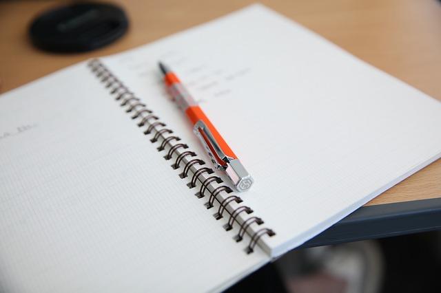 Photo d'un cahier ouvert avec un stylo