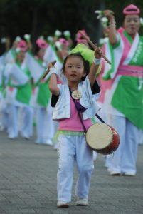 Photographie d'une fillette tapant sur un tambour dans un défilé