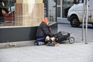 Photographie d'une femme assise au coin d'une rue avec ses paquets