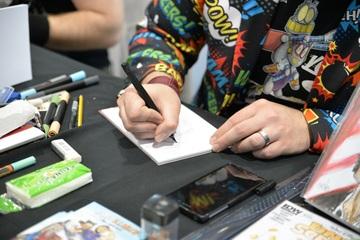 photo des mains d'un artiste en train de dessiner une BD