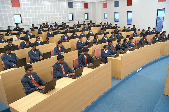 photographie d'un amphithéâtre d'élèves avec des ordinateurs