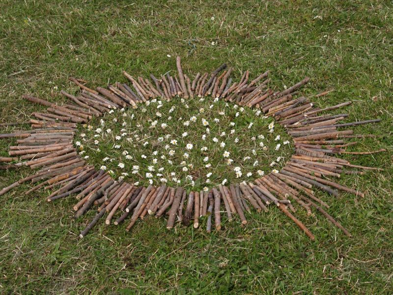 Photographie d'une oeuvre de land art batons et pierres posés en cercle dans l'herbe