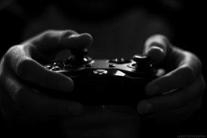 photo en noir et blanc de mains tenant une manette de jeu