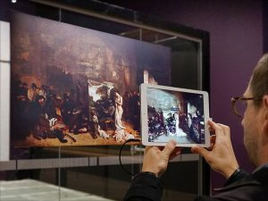 photographie d'un homme photographiant une oeuvre avec sa tablette