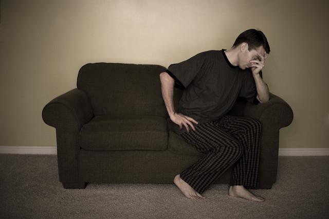 Photographie d'un homme prostré sur un canapé