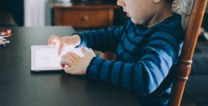 Un enfant utilise une tablette tactile