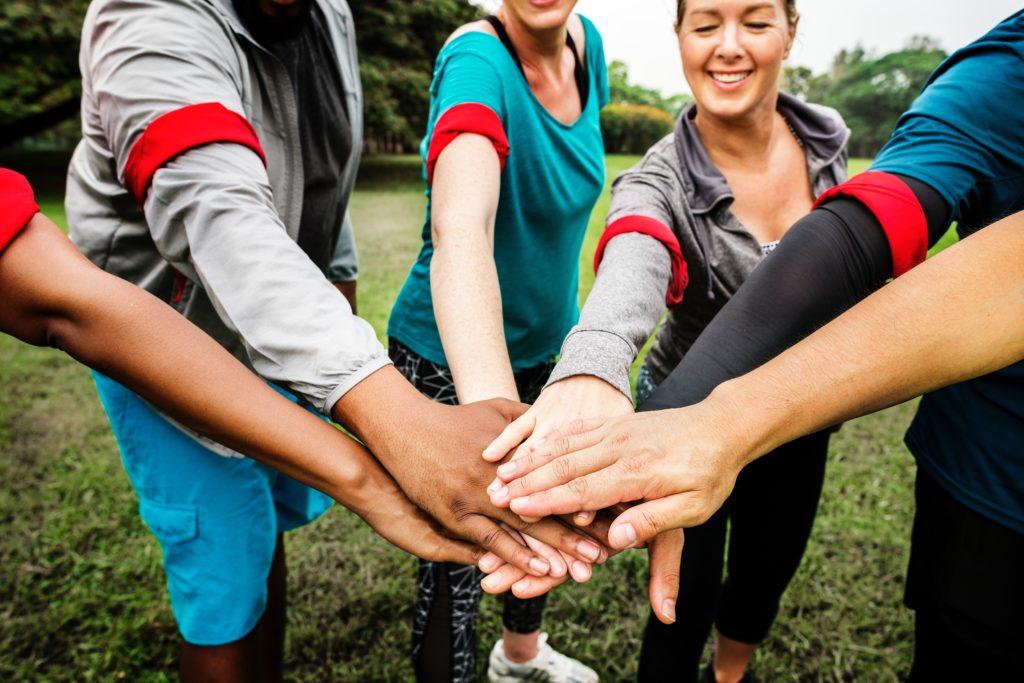 6 personnes en cercle joignent leurs mains en signe de solidarité.