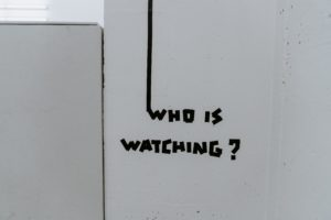 Tag mural who is watching ? en noir sur mur blanc.