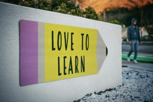 """Panneau en forme de crayon """"love to learn"""" avec un homme marchant à côté"""