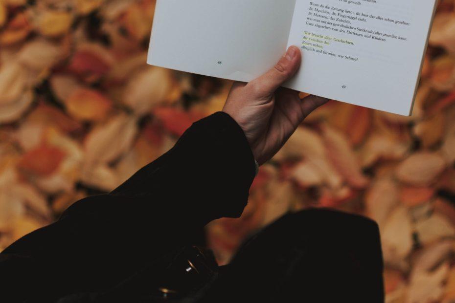 Livre ouvert sur deux poémes. Livre tenu dans une main