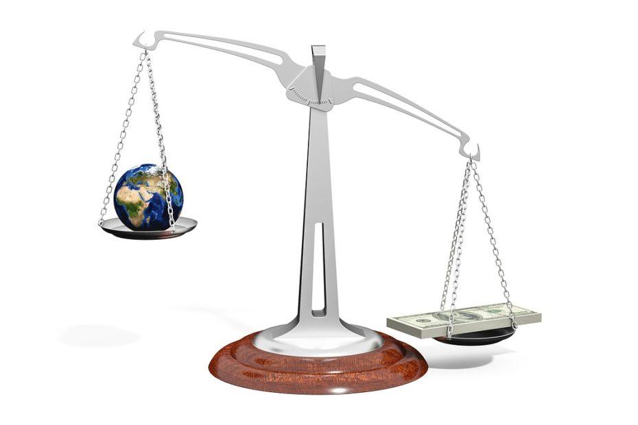 Balance pesant la planèteTerre et une liasse de billets