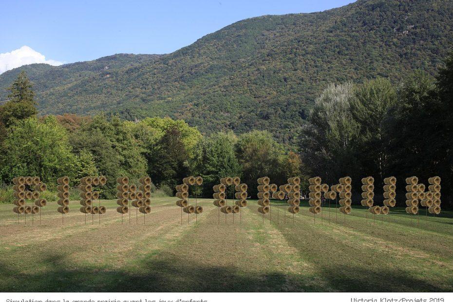 """Exemple d'installation dans une grande prairie où l'assemblage de plusieurs ballots de foin forment le texte 'Bien commun"""""""
