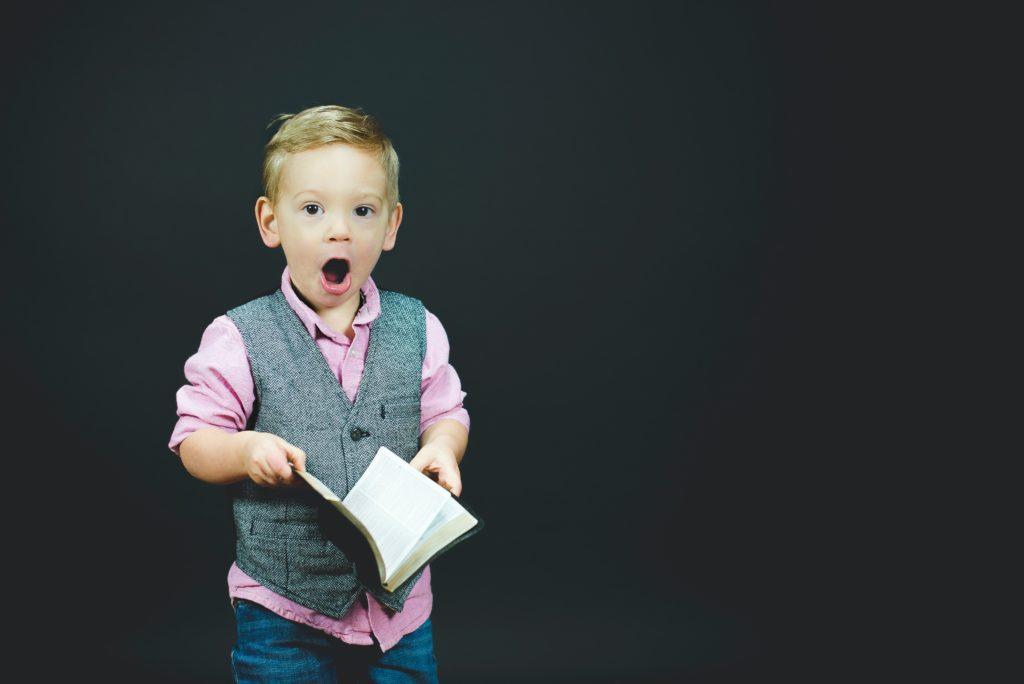 Enfant étonné qui tiens un livre ouvert