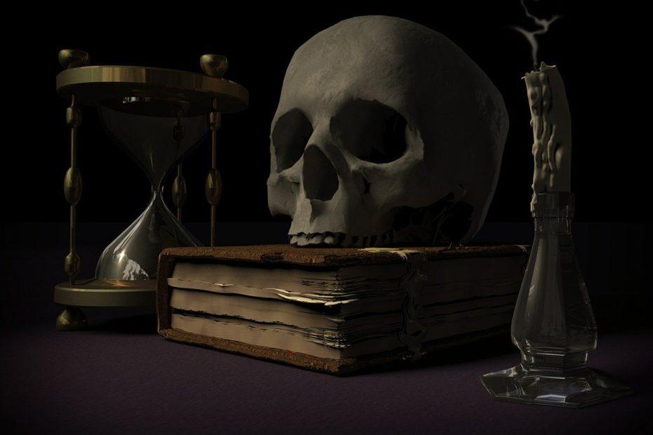Sablier symbolisant le temps qui passe, un crâne humain posé sur un livre, une bougie éteinte.