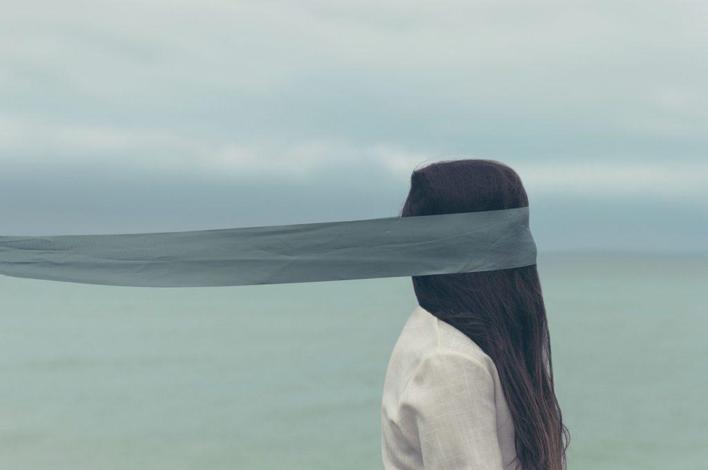Face à la mer, une femme avec les cheveux qui retombent devant son visage et un ruban autour des yeux