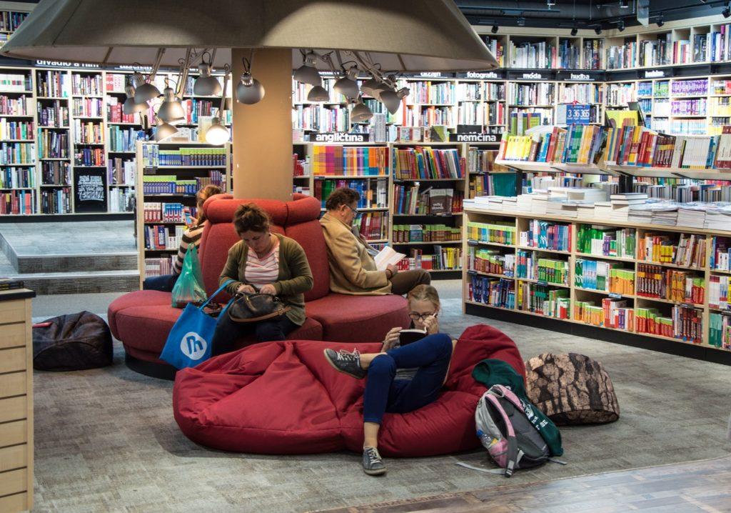 Intérieur d'une bibliothèque avec des usagers lisant dans des poufs