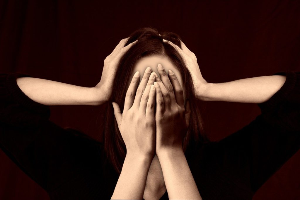 Femme qui se cache les yeux avec les mains