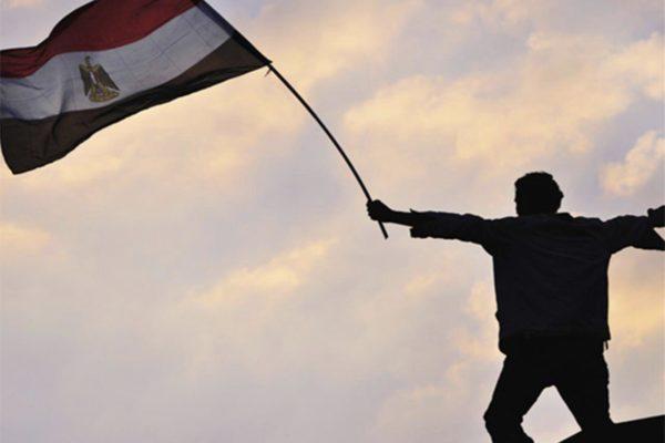 Homme debout dans le crépuscule, levant le drapeau égyptien