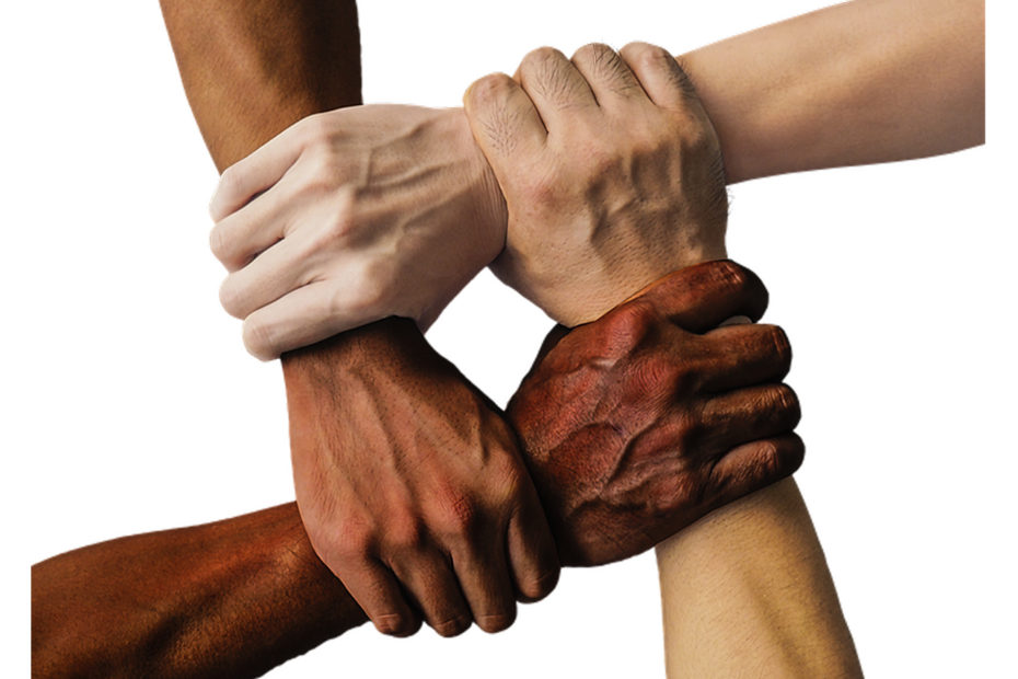 4 bras de différentes couleurs se tenant par le poignet
