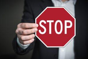 Main d'homme montrant un grand panneau STOP